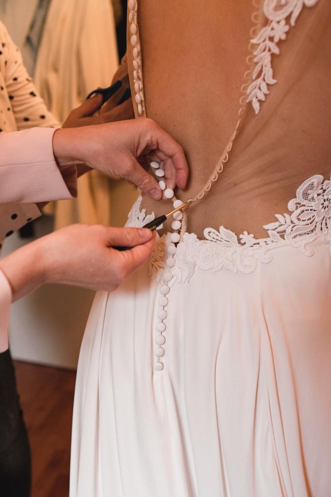 Traunzeugin macht das Brautkleid der Braut zu.