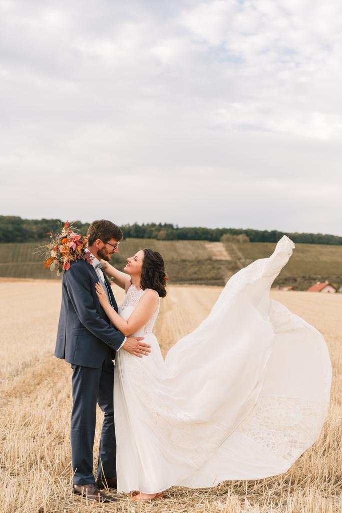 Hochzeitspaar steht auf einem Feld und die Schleppe fliegt im Wind.
