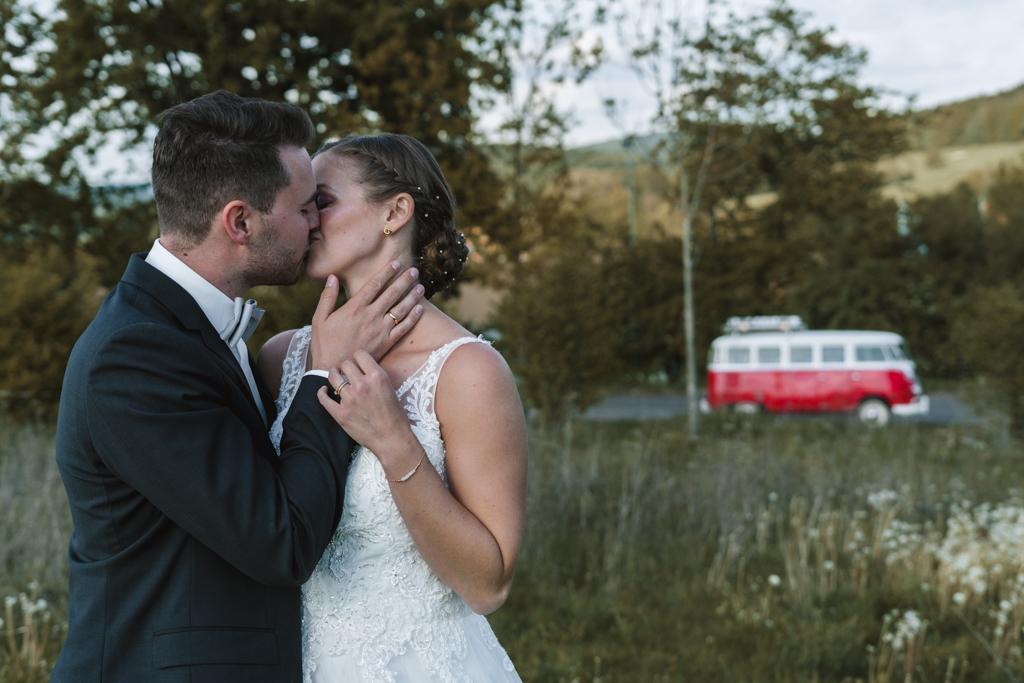 Brautpaar im Vordergrund küsst sich, im Hintergrund ein weiß-roter Vw Bus.