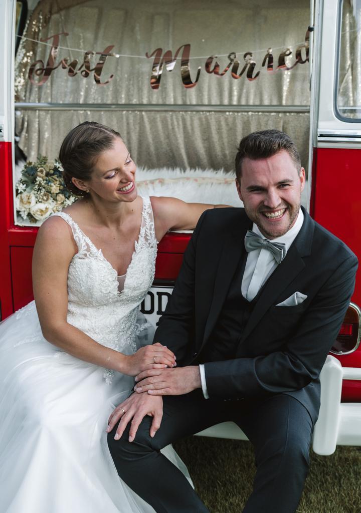 Brautpaar sitzt im Kofferraum von einem VW-Bus und lacht miteinander.