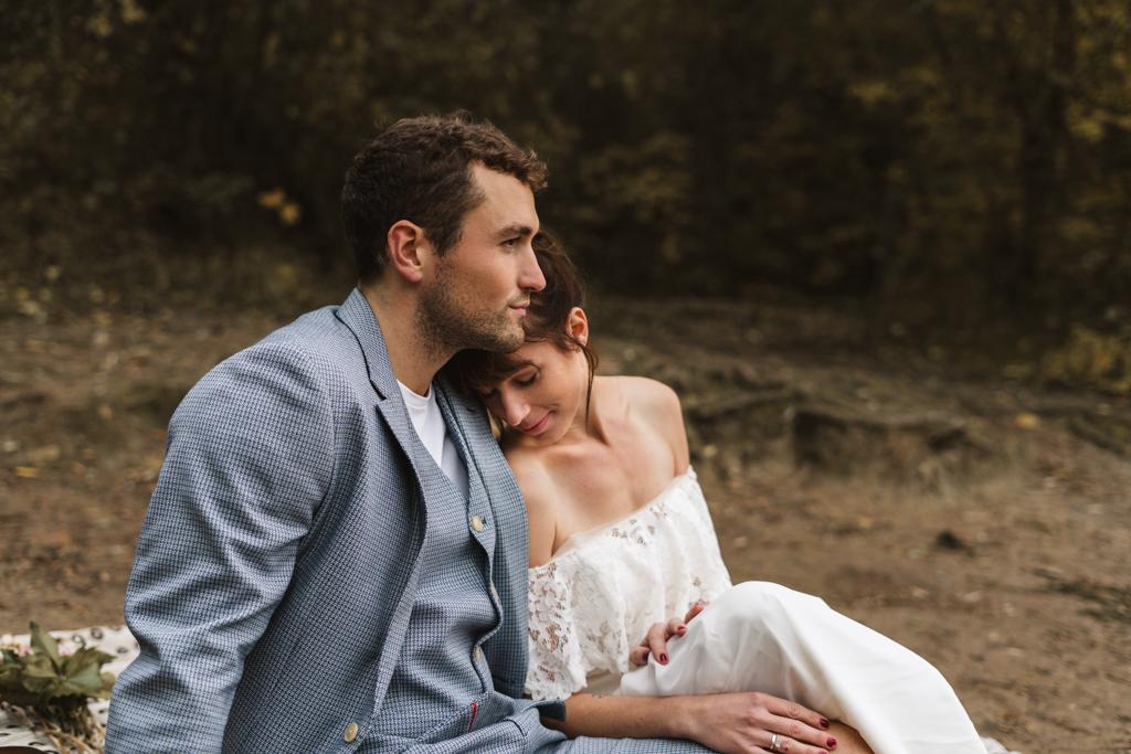 Braut sitzt angekuschelt an der Schulter ihres Bräutigam an einem Strand.