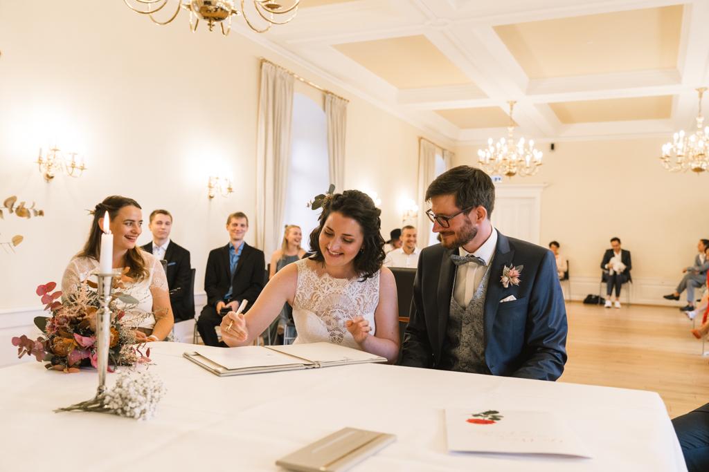 Braut unterschreibt das Ehegelöbnis und lacht.