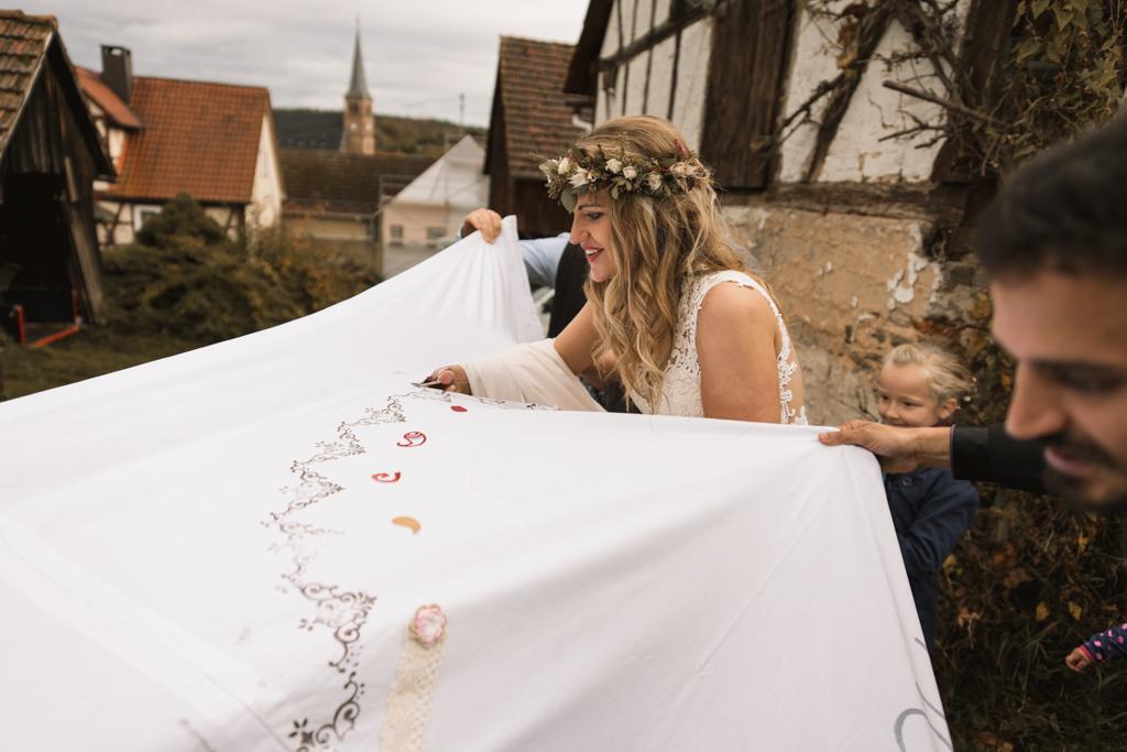 Braut zerschneidet mit Hochzeitslacken mit einer Nagelschere.