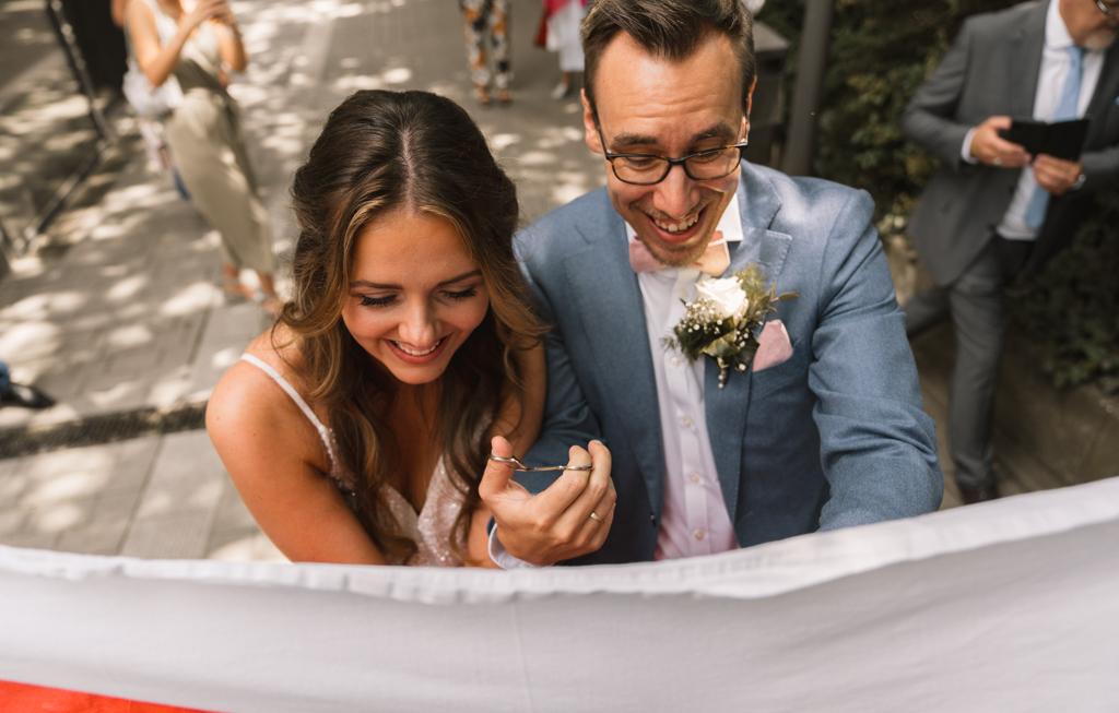 Brautpaar mit das Herz aus einem Lacken mit einer Nadelschere schneiden.