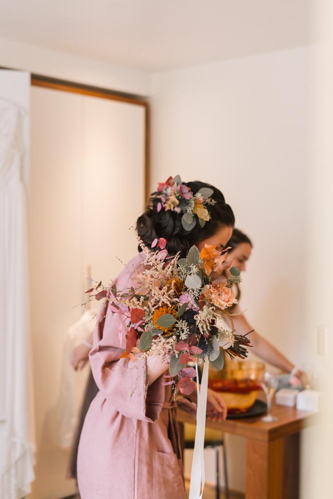 Braut beim Getting Ready mit Hochzeitsstrauß und Blumenhaarschmuck.