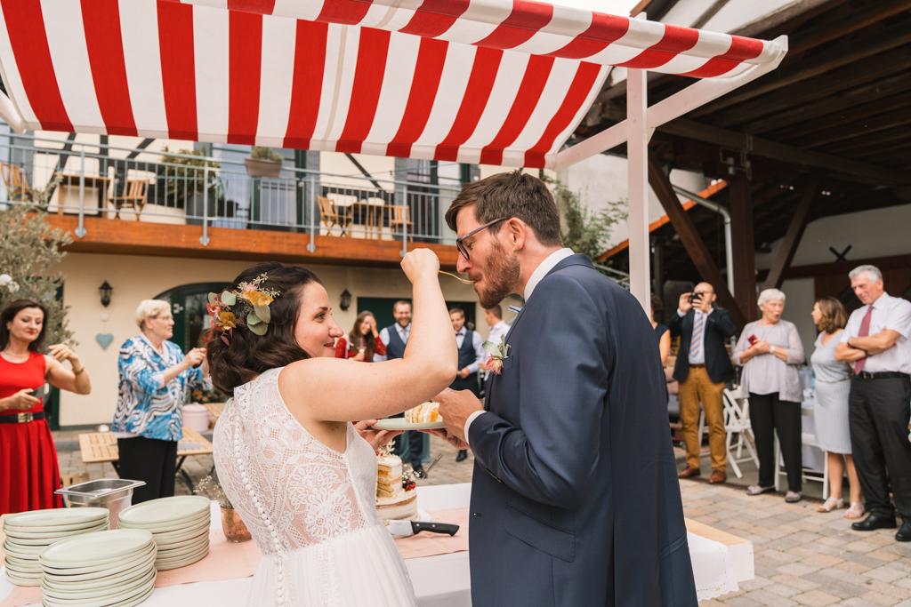 Brautpaar fttert sich mit der Hochzeitstorte.