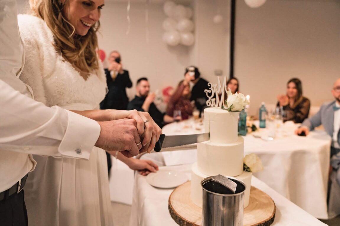 Brautpaar schneidet gemeinsam die Hochzeitstorte an
