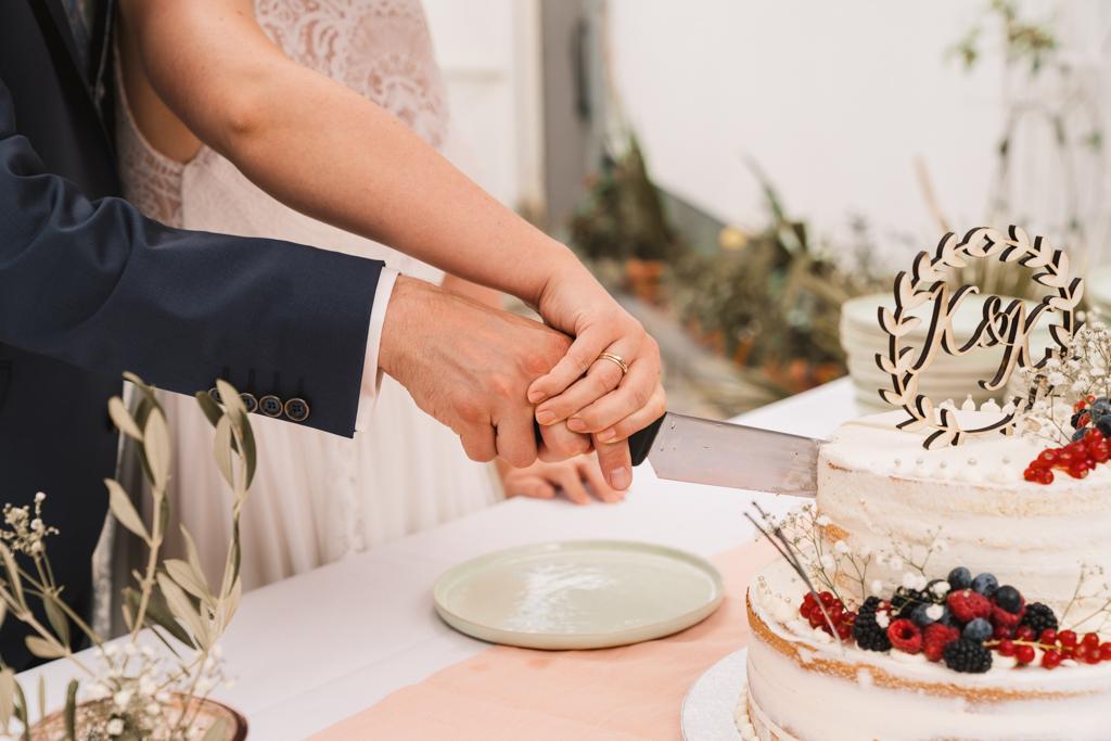 Hände vom Brautpaar beim Hochzeitstorten Anschnitt.