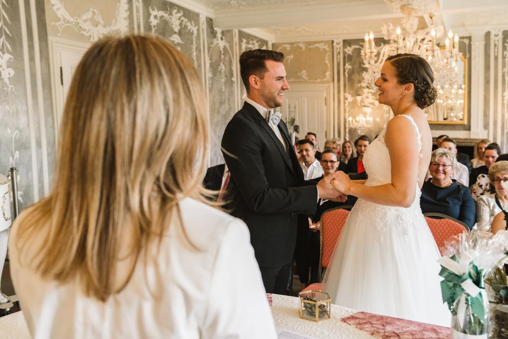 Brautpaar steht vor der Standesbeamtin und gibt sich das Ja-Wort.