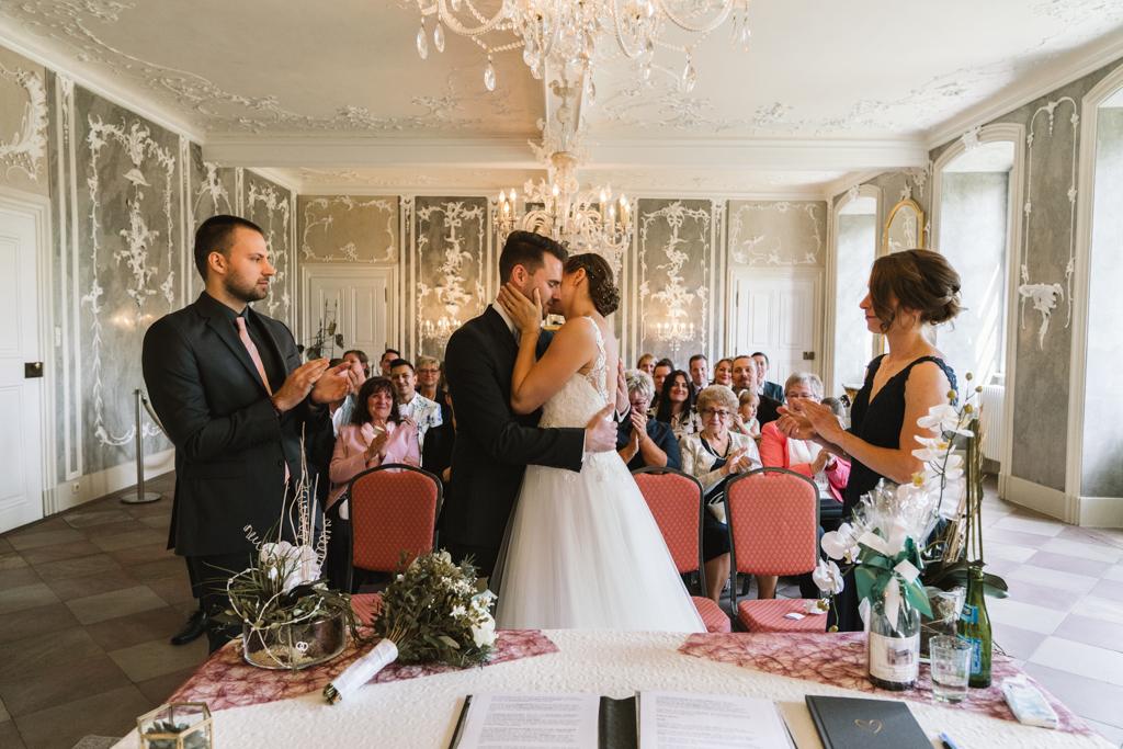 Brautpaar umarmt sich und die Hochzeitsgesellschaft klatscht während der Trauung.