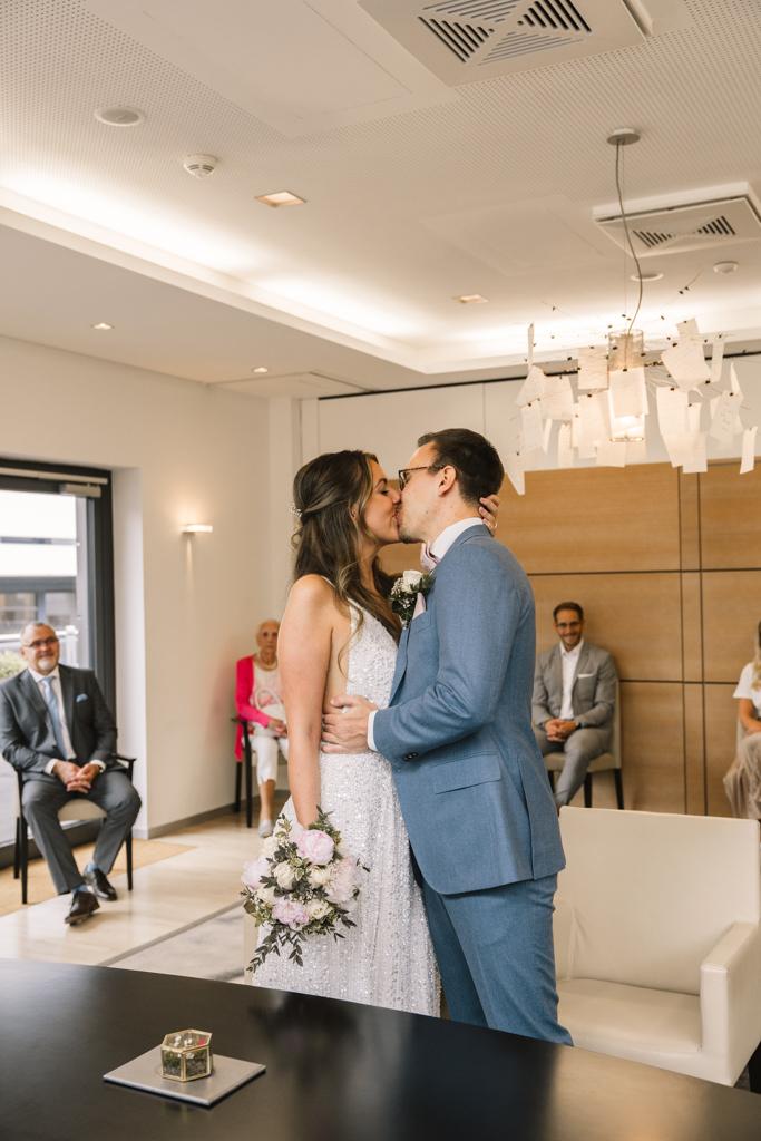 Brautpaar küsst sich als Mann und Frau im Standesamt.