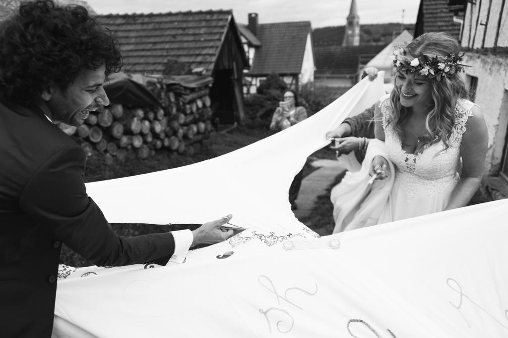 Hochzeitspaar zerschneidet ein Lacken mit der Nagelschere.