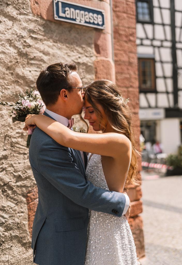 Brautpaar steht in der Langegasse und küsst sich.