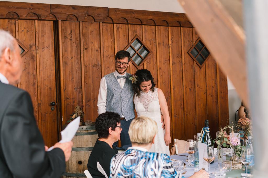 Opa hält eine Hochzeitsrede und das Brautpaar steht vor einer Scheune.