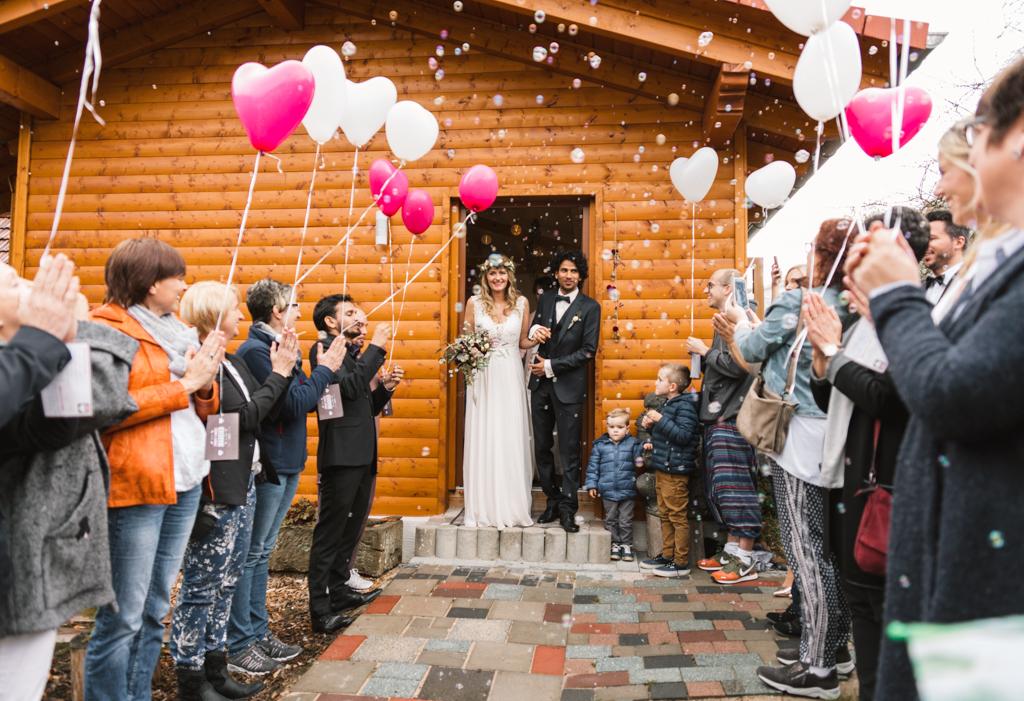 Brautpaar läuft nach der Trauung aus und wird von der Hochzeitsgesellschaft mit Seifenblasen und Luftballons begrüßt.