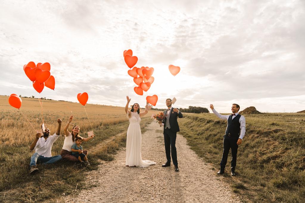 Hochzeitsgesellschaft und das Hochzeitspaar lassen rote Luftballons los.