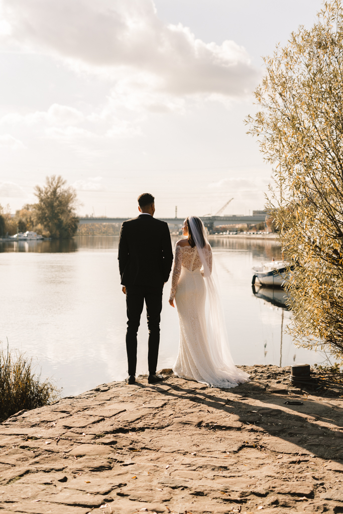 Hochzeitspaar steht an der Landzunge vom Main und schaut auf Wasser.