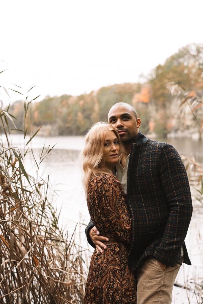 Liebespaar steht eng umschlungen an einem See beim Paarshooting.