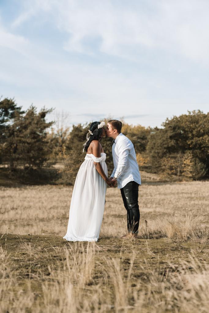 Pärchen küsst sich auf einer Wiese im weißen Kleid und blauem Hemd.