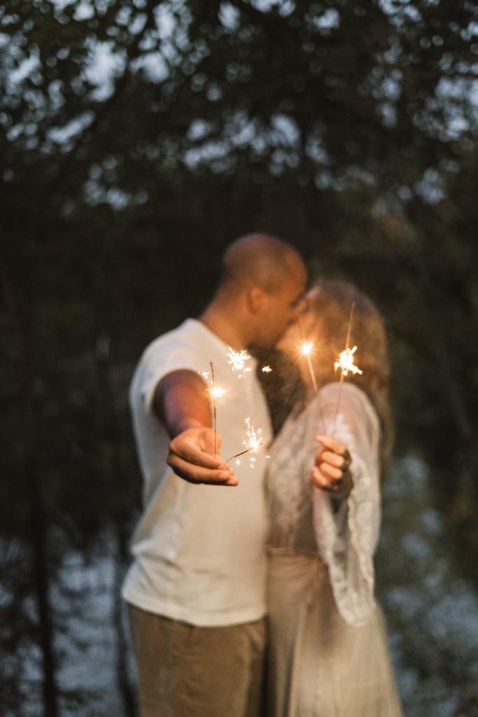 Pärchen küsst sich während des Paarshooting und halten Wunderkerzen in den Händen.