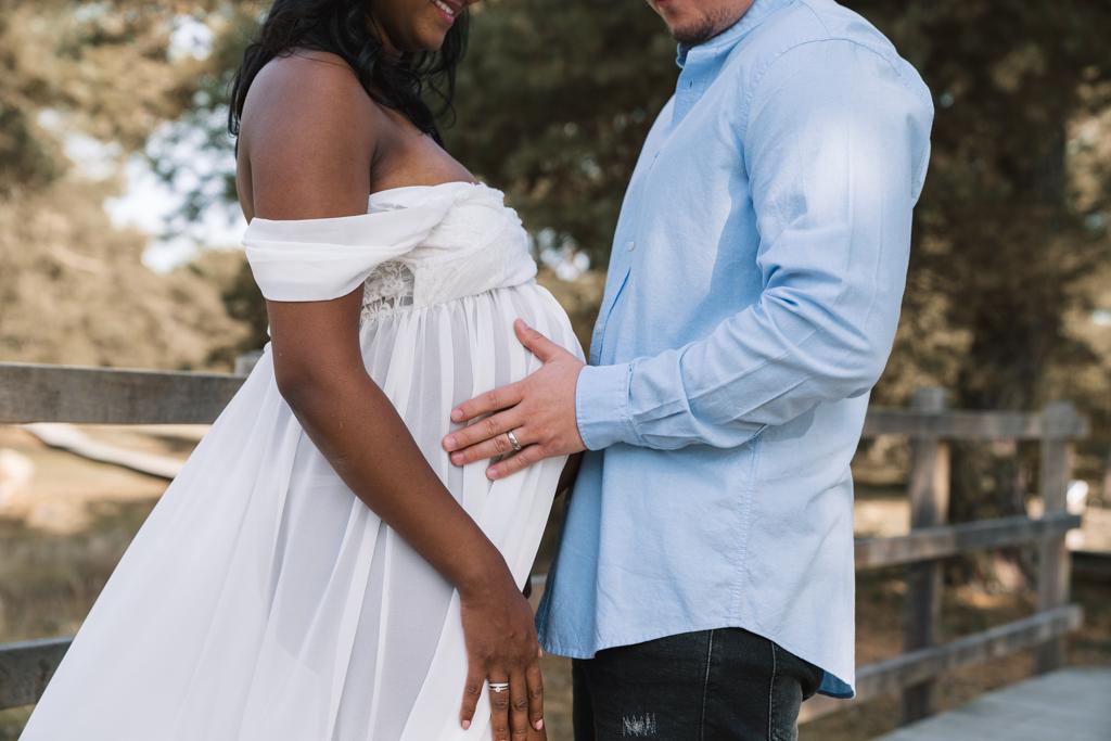 Papa hält den Babybauch im weißen Kleid sanft fest.