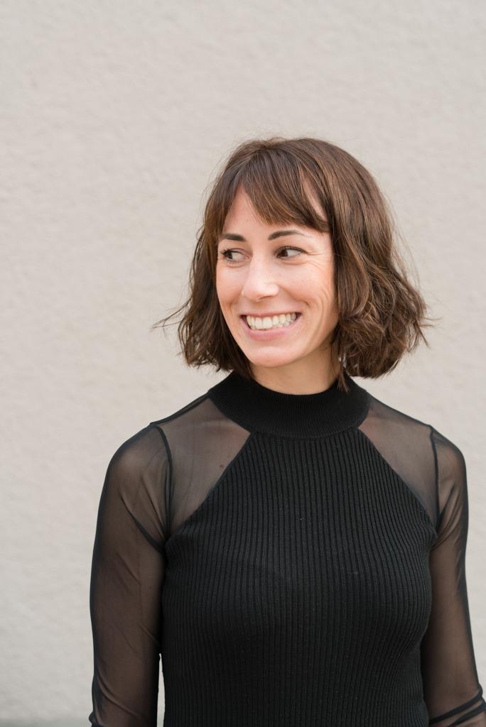 Portrait einer brünetten Frau mit schwarzen Oberteil.