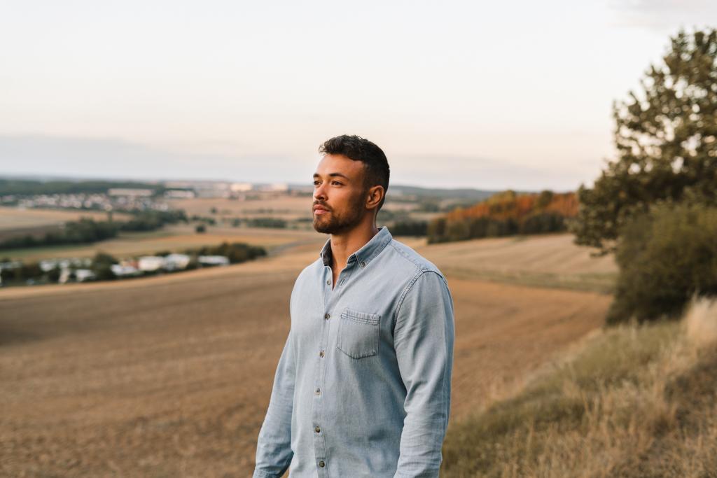 Mann steht auf einem Feld und schaut in die untergehende Sonne.