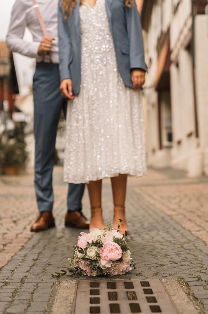 Brautstrauß liegt auf den gepflasterten Boden.