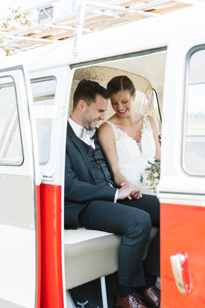 Brautpaar in weiß-rotem Retro Bus und schaut sich die neuen Eheringe an.