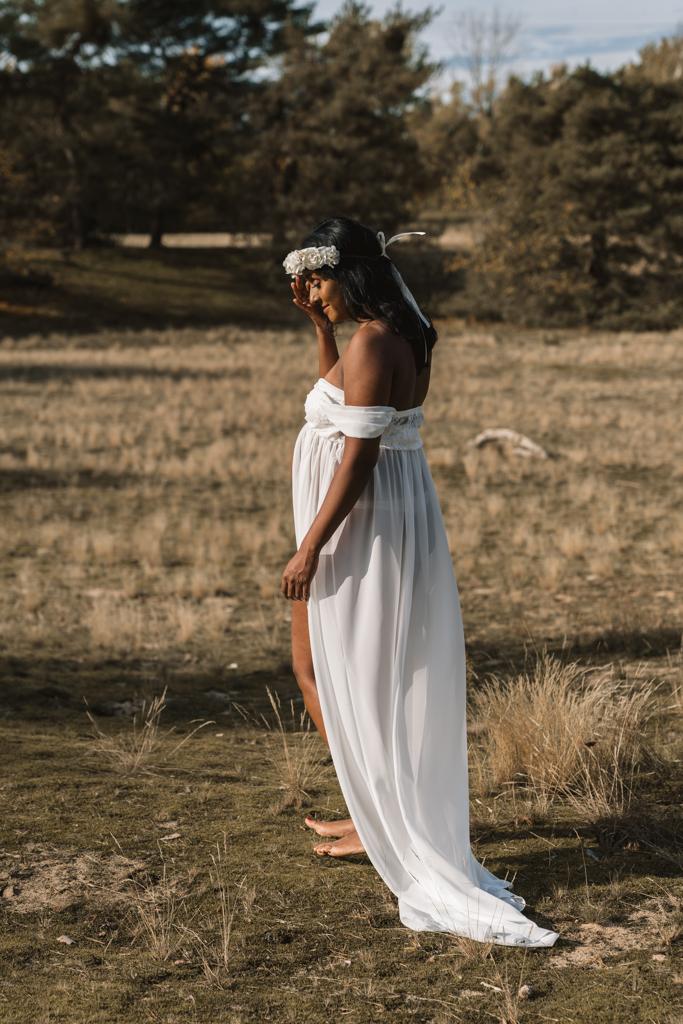Braut steht in den Dünen im weißen Kleid und Haarkranz.