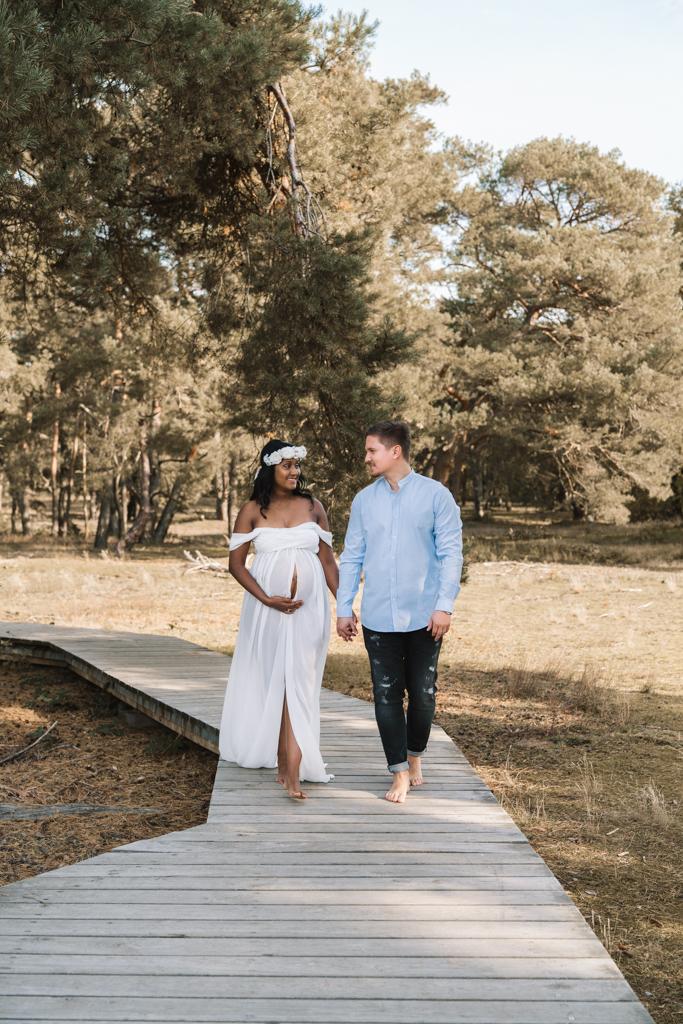 Schwangeres Paar läuft einen Steg in den Dünen entlang.
