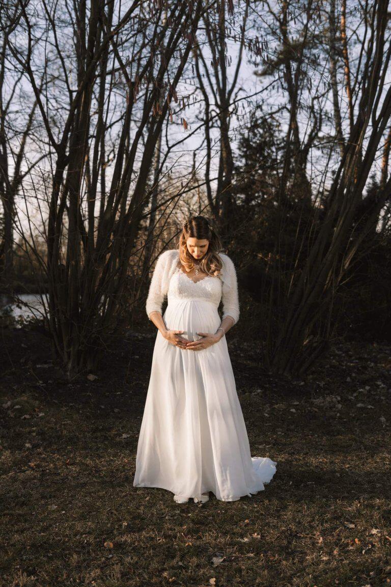 Braut steht bei untergehenden der Sonne draußen und hält unter ihrem Brautkleid den Babybauch in den Händen