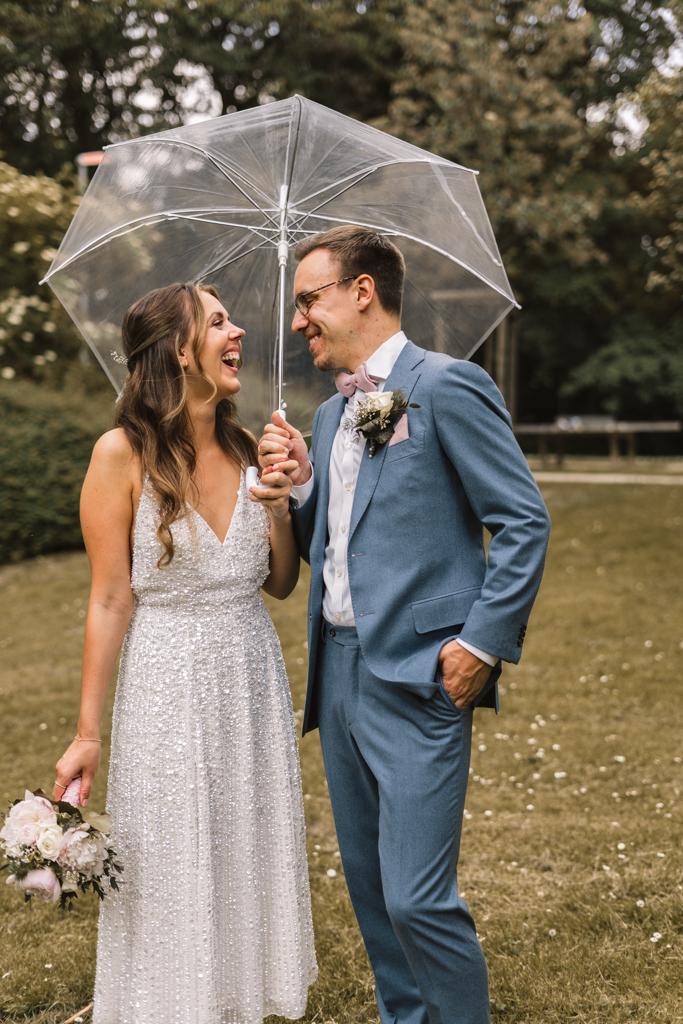 Brautpaar steht unter einem durchsichtigen Regenschirm und lacht.