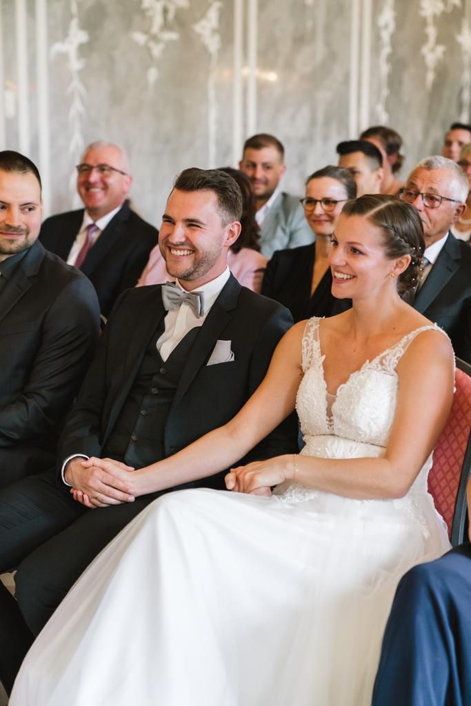 Brautpaar hält während der Hochzeit die Hände und lacht.