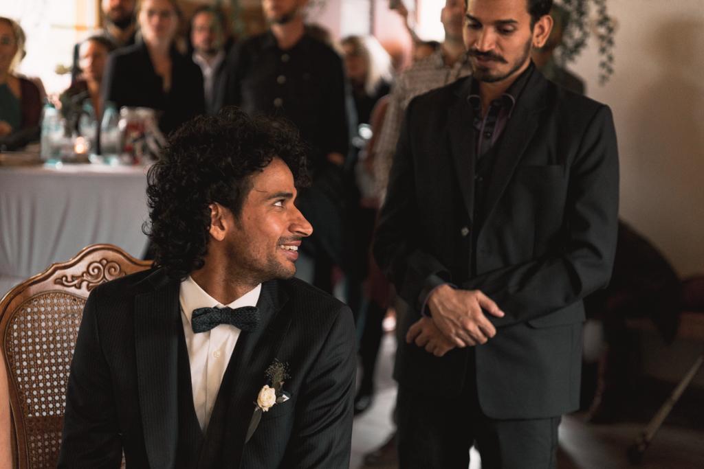 Bräutigam lacht seinen Trauzeugen an.