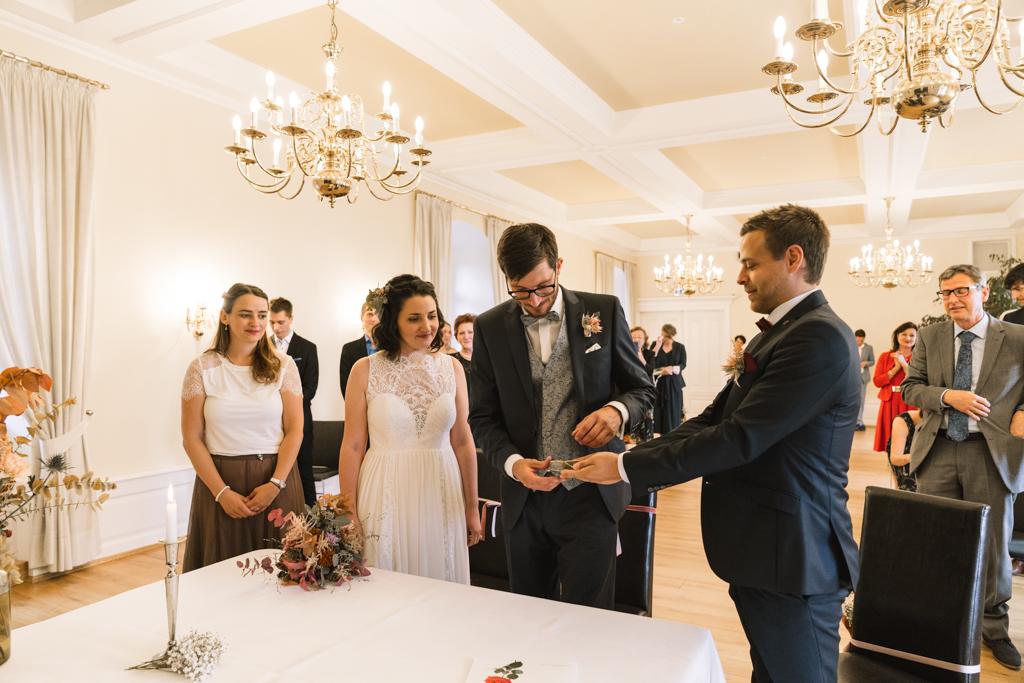 Trauzeuge überreicht die Ehering an das Brautpaar.