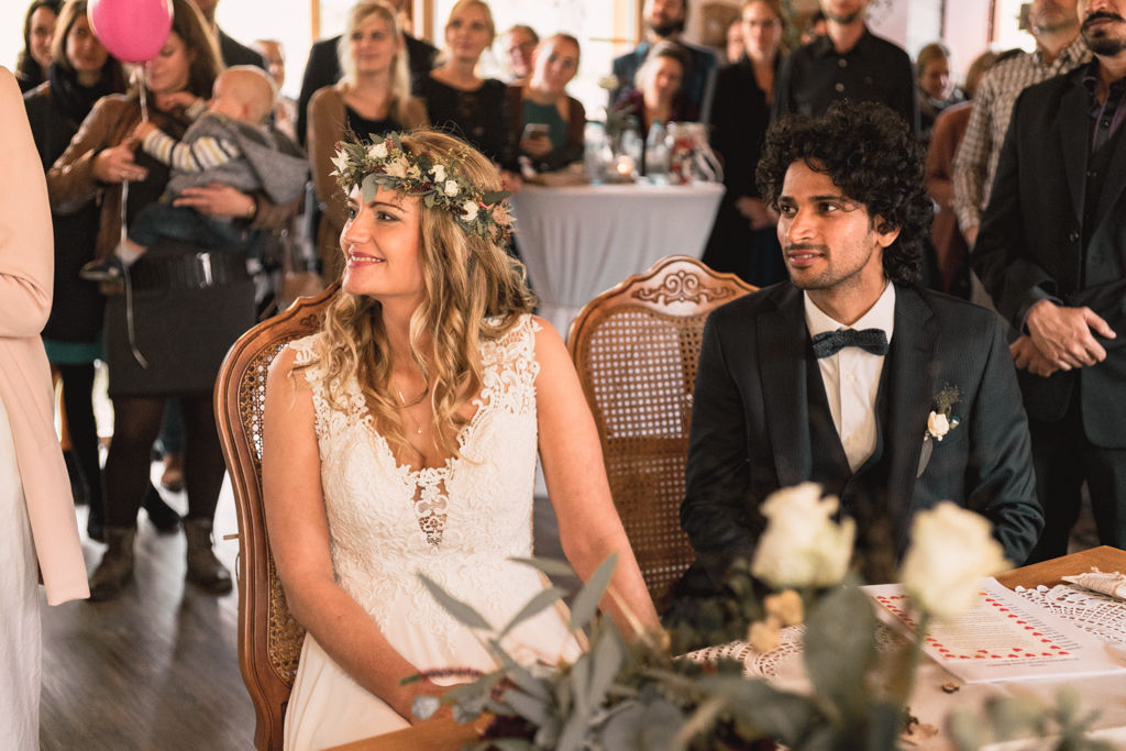 Hochzeitspaar während der freien Trauung auf der Yoga Alm am lachen.