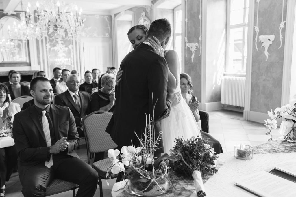 Schwarz weiß Bild von einem Brautpaar was sich während der Trauung umarmt.