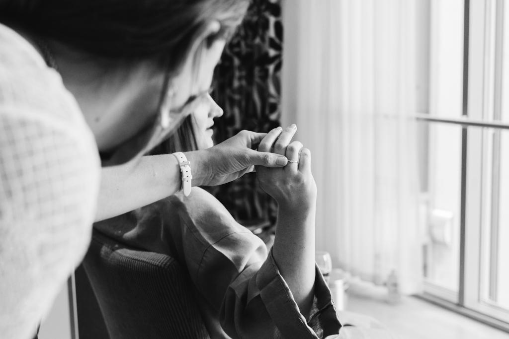 Trauzeugin schaut sich den Verlobungsring der Braut an.