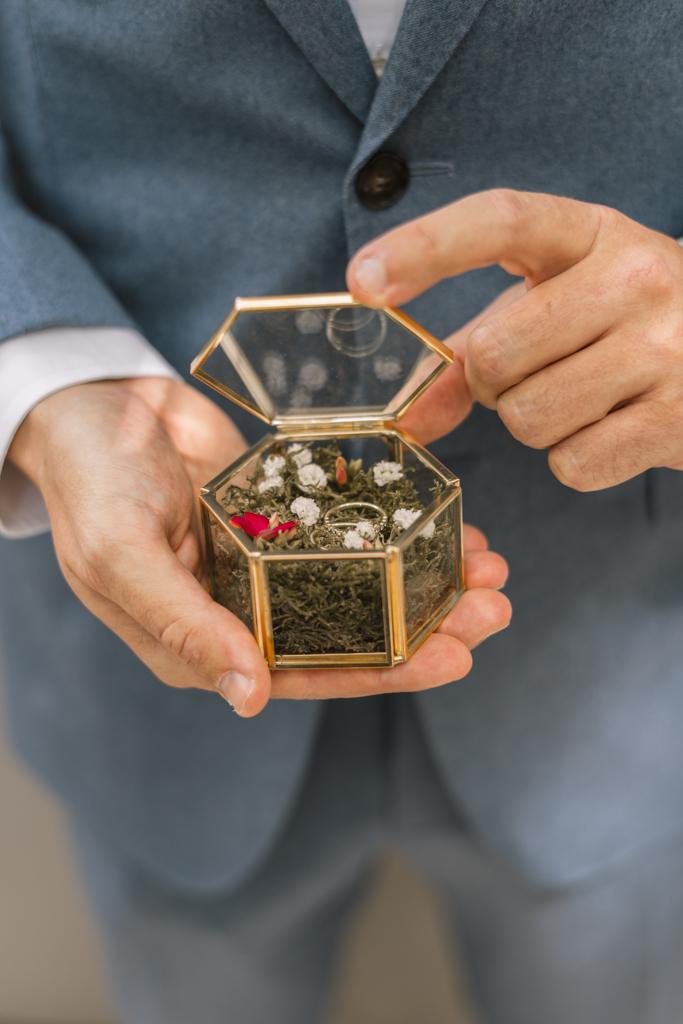 Bräutigam hält Ringschachtel mit den Eheringen in der Hand.