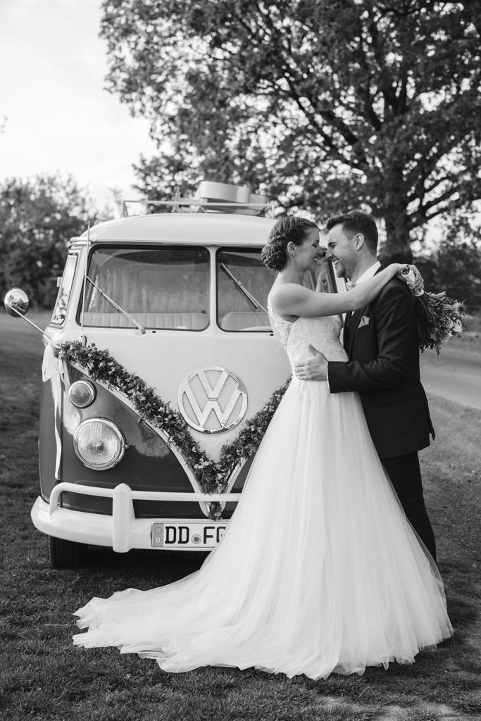 Brautpaar lacht miteinander vor einem VW-Bus.