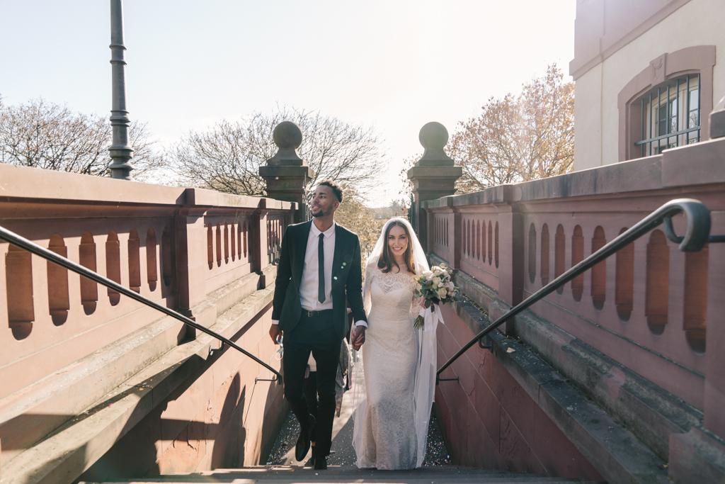 Brautpaar läuft die Treppe zum Standesamt hoch.