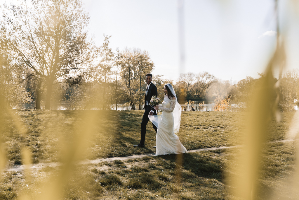 Brautpaar lauft einen Wiesenweg zum Standesamt.