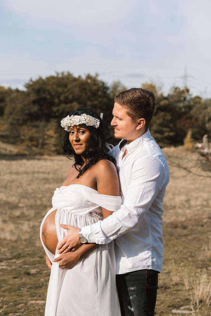 Papa hält von hinten den Babybauch seiner Frau im weißen Kleid.