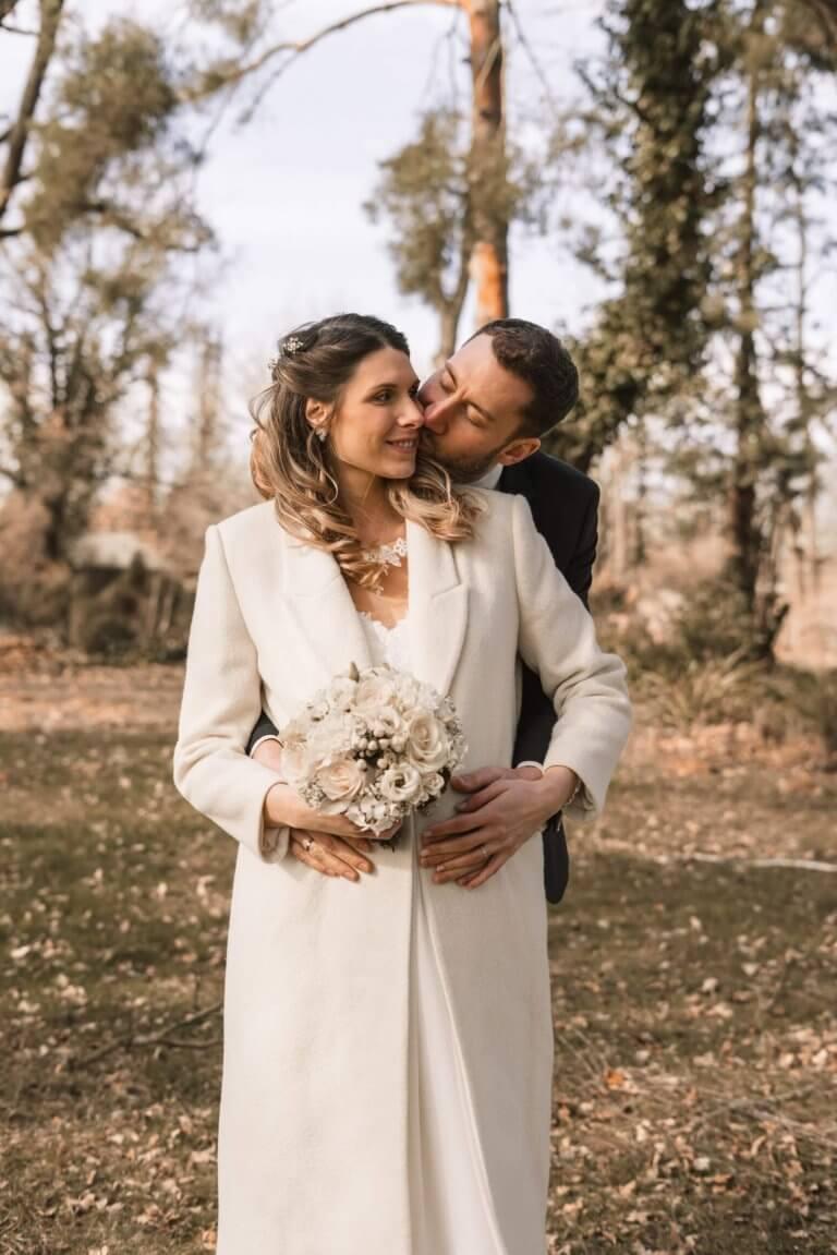 Winterhochzeit Brautpaarshooting Bräutigam küsst seine Braut auf die Backe