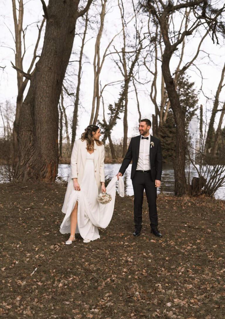 Brautpaar steht vor einem See während des Brautpaarshootings