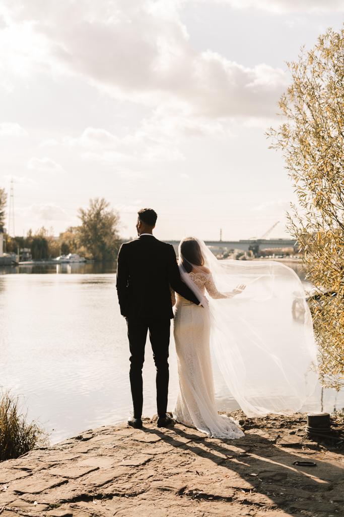 Brautpaar steht am Main und Braut lässt ihre Schleppe im Wind wehen.