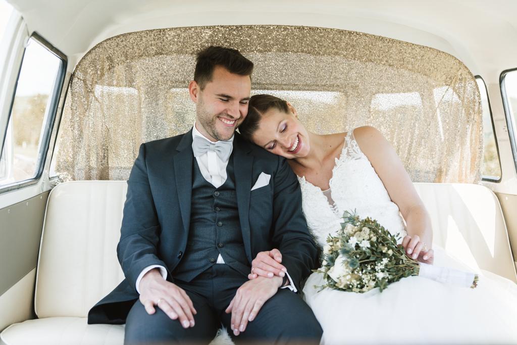 Brautpaar sitzt im cremefarbenen Brautwagen.