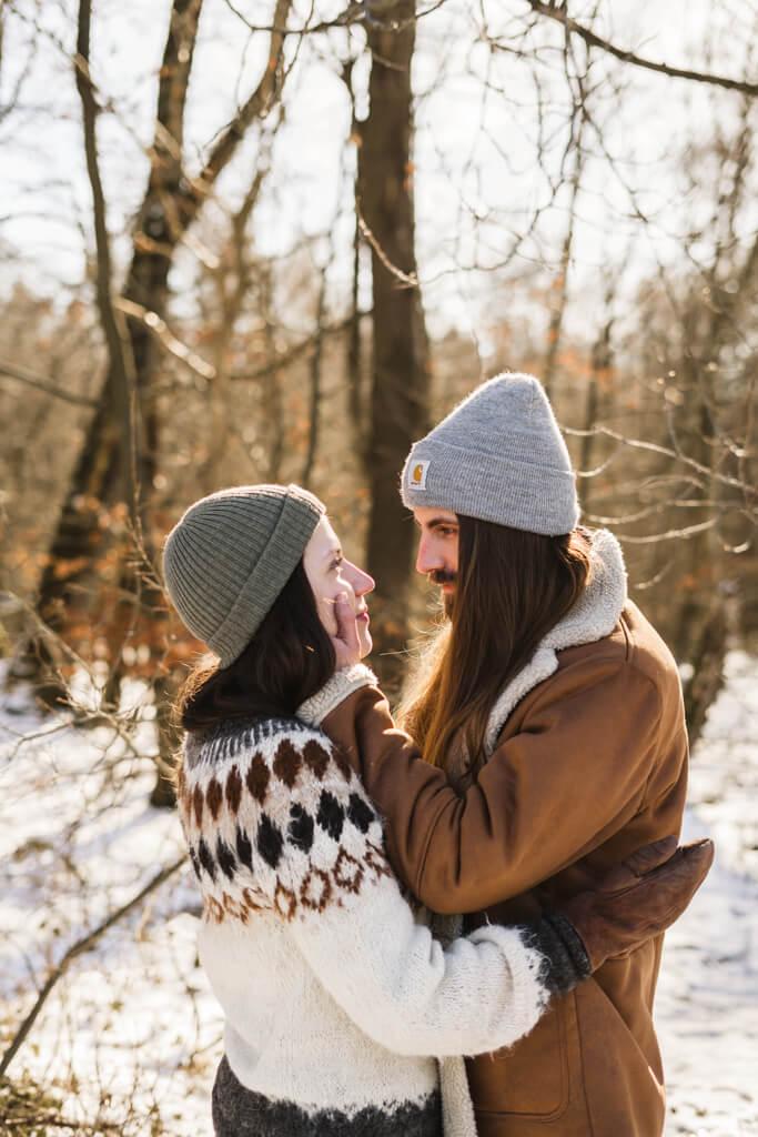 Paar steht im Schnee und hält sich in den Armen und schaut sich tief in die Augen.