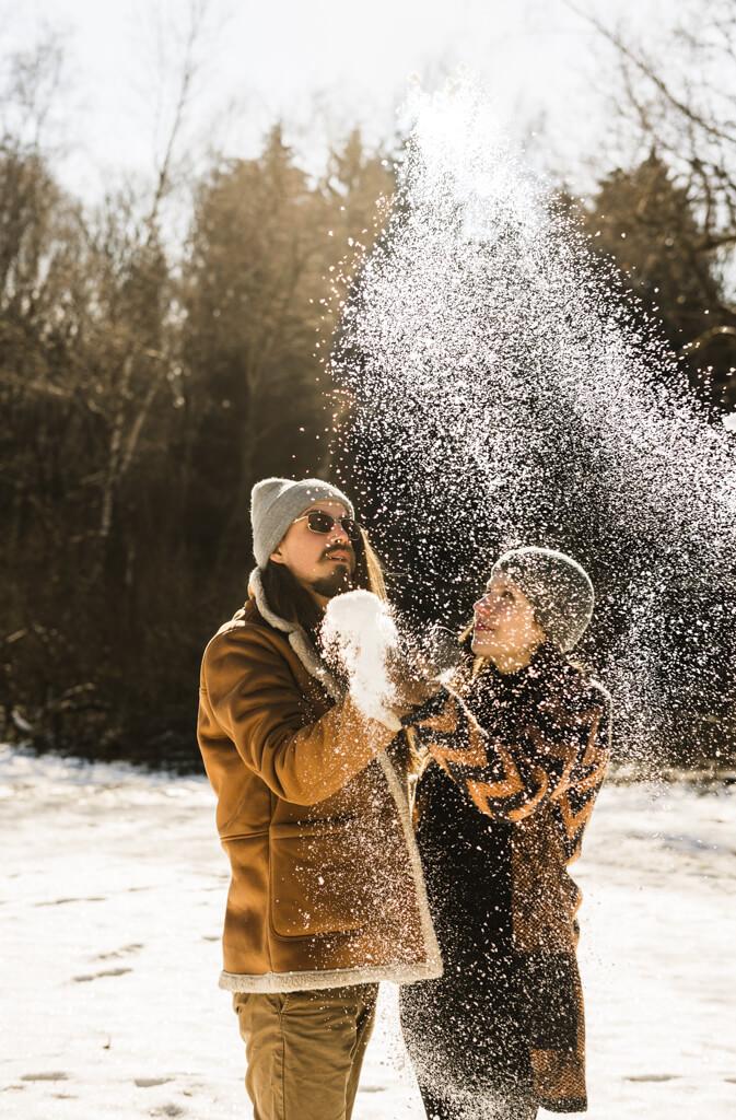Paar steht im Schnee und wirft einen Schneeball in die Luft.